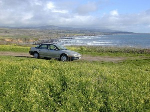 Image of a salvage car by the ocean.